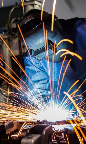 Industrial worker is welding car in factory